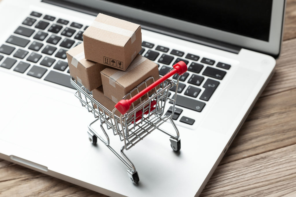 Delivery of the order from the online store. Online shopping. Boxes with goods in the shopping basket on the table with laptop.