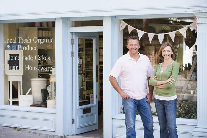 Two retail owners in front of their business with a retail strategy that makes them successful
