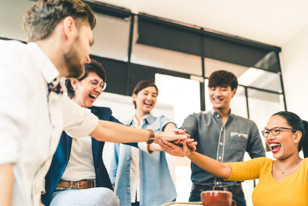 Multiethnic diverse group of happy colleagues join hands together illustrating the rewards successful POS resellers could reap in 2018 by following the following tips.