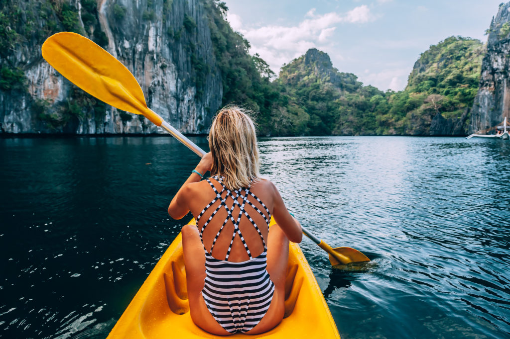 Woman paddling a kayak that exemplifies the latest technology and design in water sports and surf shop retail trends.