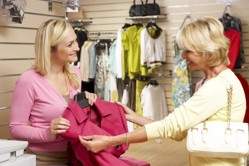 A nice young clothing retailers sales associate assisting a customer in a clothing store.