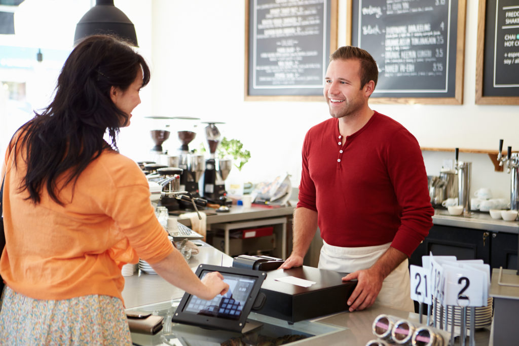 A young man smiling behind a counter and wearing an apron takes the order of a woman with the help of his coffee shop point of sale software