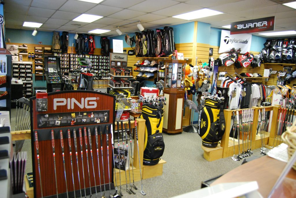 The interior of a golf themed retailer featuring related sports items and pro shop point of sale desk