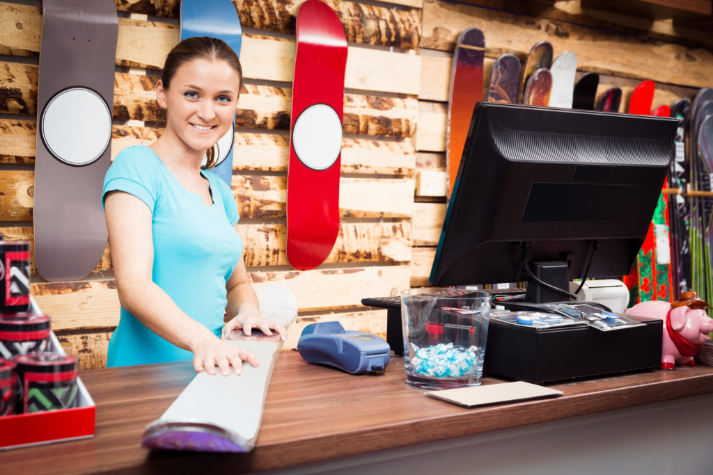 salesperson standing at cash register in ski store preparing merchandise to align with this year's snow sports consumer trends