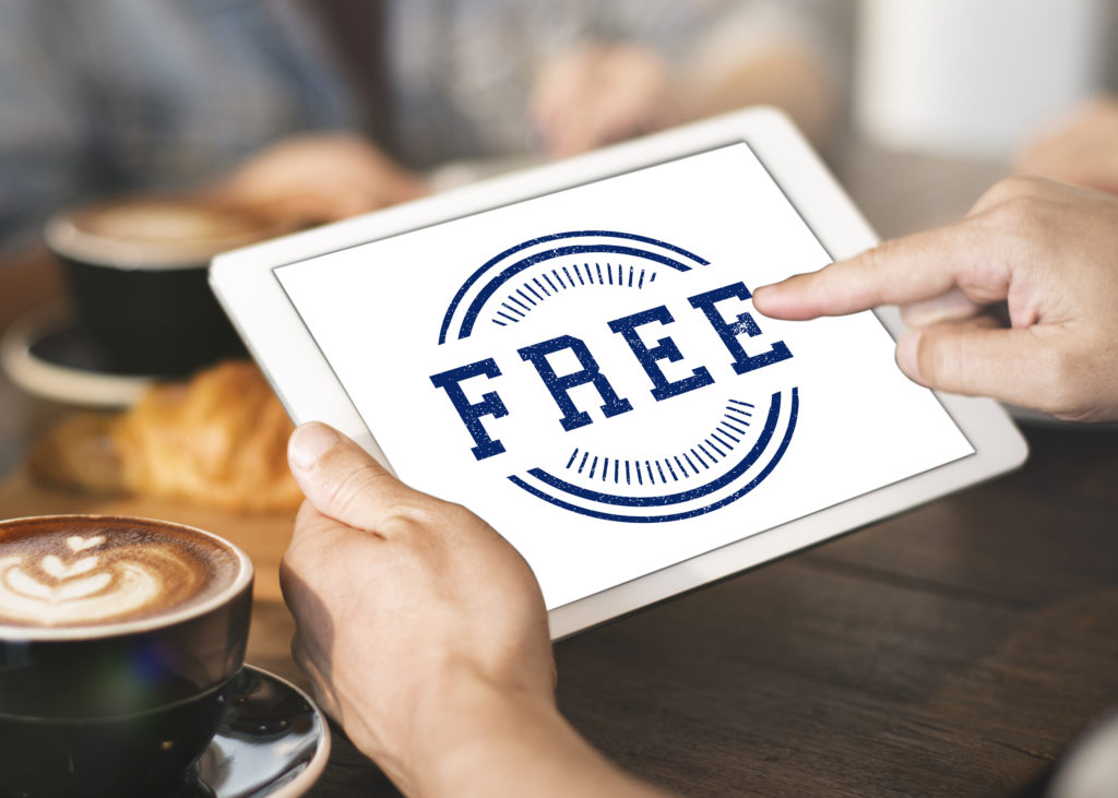 Hands holding a tablet in a restaurant and on the screen is the word Free, for an article that demonstrates the pitfalls of free POS systems.